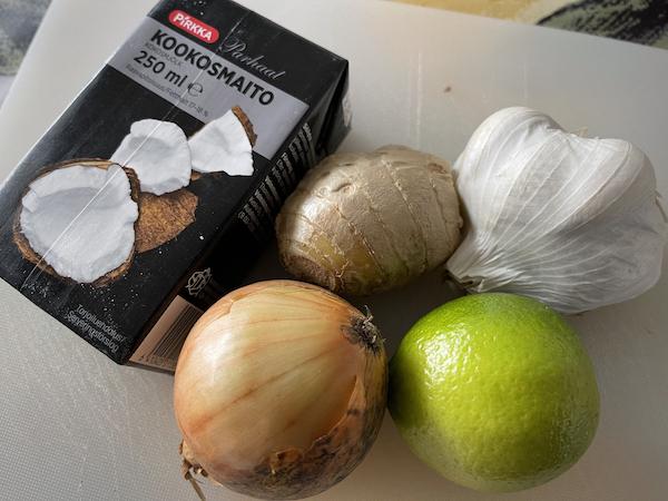 Kookosmaitopurkki, sipili, inkivääri ja valkosipuli leikkuulaudalla