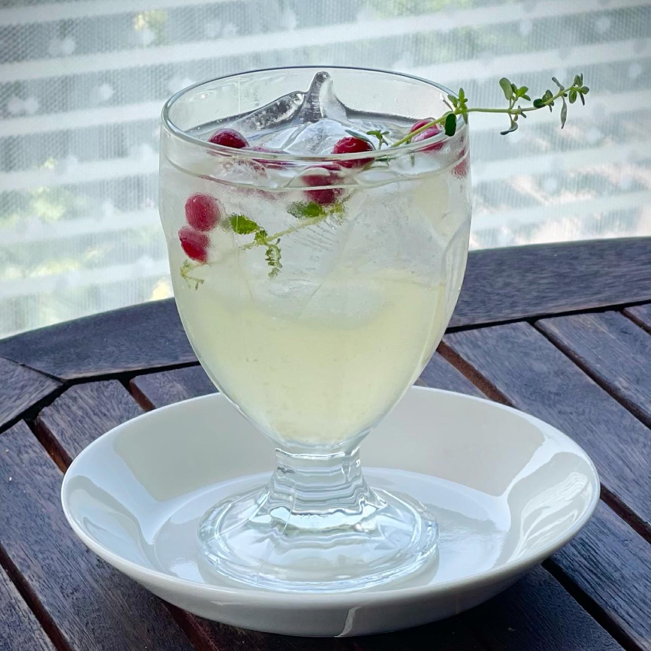 Valmis juoma jalallisessa juomalasissa. Koristeena timjaminoksa ja puolukoita